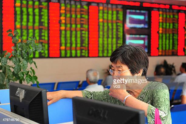 An investor observes stock market at a stock exchange hall on July 7 2015 in Fuyang Anhui Province of China Chinese shares rebounded to 3700 points...