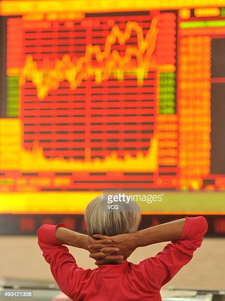 An investor observes stock market at a stock exchange hall on October 20 2015 in Fuyang Anhui Province of China The CSI300 index of the largest...