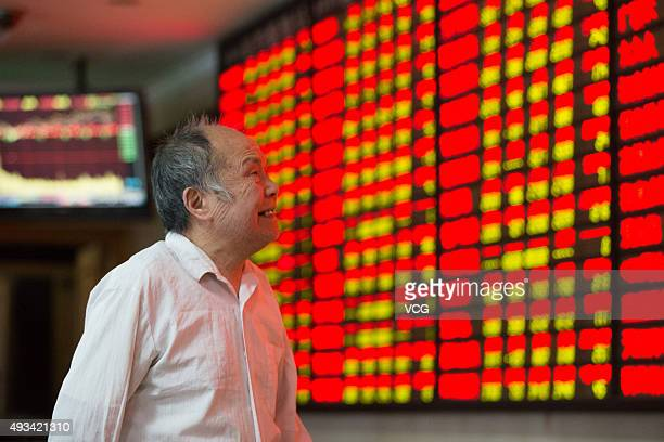 An investor observes stock market at a stock exchange hall on October 20 2015 in Nanjing Jiangsu Province of China The CSI300 index of the largest...