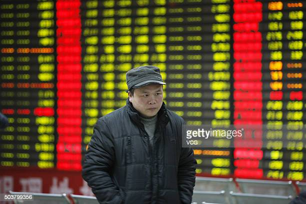 An investor observes stock market on January 7 2016 in Huaibei Anhui Province of China Chinese shares slumped to a halt in half an hour on Thursday...