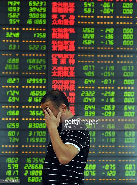 An investor reacts in front of a screen showing stock market movements in Fuyang eastern China's Anhui province Chinese shares took another tumble on...