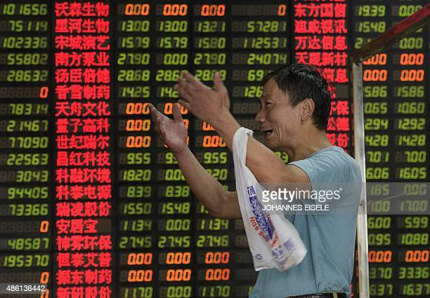 An investor reacts in front of screens showing stock market movements at a brokerage house in Shanghai on September 1 2015 Shares in Hong Kong and...