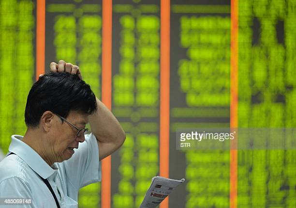 An investor reads a newspaper before a screen showing share prices at a securities firm in Hangzhou in eastern China's Zhejiang province on August 24...