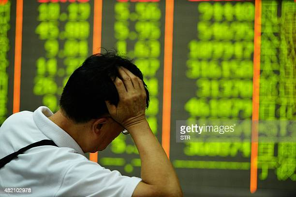 An investor rests on his arm before a screen that shows share prices in a security firm in Hangzhou east China's Zhejiang province on July 27 2015...