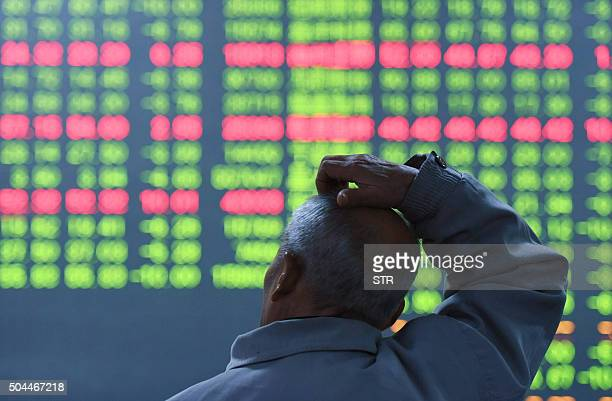 An investor sits in front of a screen showing stock market movements at a securities firm in Hangzhou in eastern China's Zhejiang province on January...