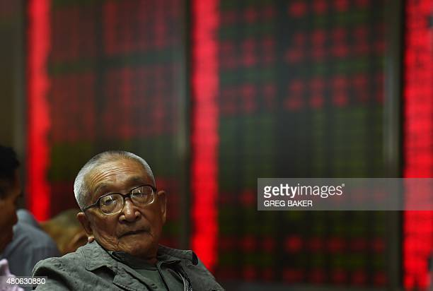An investor sits in front of screens showing stock market movements at a securities company in Beijing on July 14 2015 Hundreds of firms were...