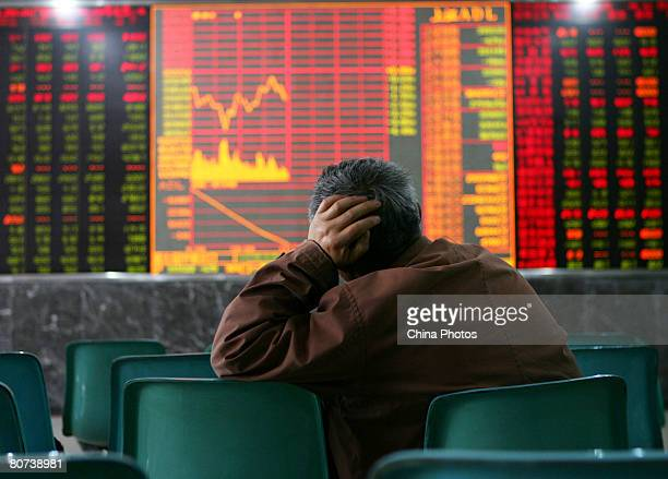 An investor views stocks at a securities company on April 18 2008 in Wuhan of Hubei Province China Chinese stocks fell sharply today amid continued...