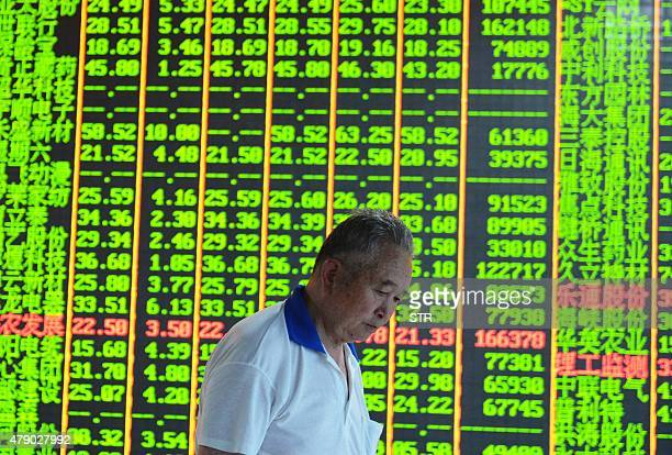 An investor walks past a share prices board at a security firm in Hangzhou eastern China's Zhejiang province on June 30 2015 AFP PHOTO CHINA OUT