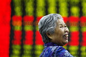 An investor watches the eclectic monitor at a stock exchange in Huaibei Anhui province China on 29th June 2015 The Shanghai Composite fell 33% to...