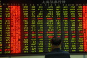An investor watches the electronic board at a stock exchange hall on May 25 2011 in Dalian Liaoning Province of China Chinese stocks closed down on...