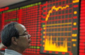 An investor watches the electronic board at a stock exchange hall on June 14 2011 in Huaibei Anhui Province of China International markets have been...