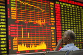 An investor watches the electronic board at a stock exchange hall on June 24 2013 in Huaibei China Chinese shares dropped remarkably on Monday The...
