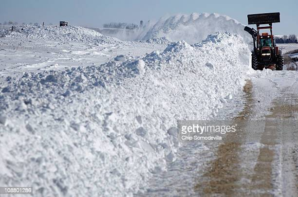 An Iowa State Department of Transportation tractor uses a snowblower to move a wall of snow off of Highway 30 February 3 2011 east of Cedar Rapids...