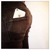 An iPhone 5 tucked into the back pocket of a woman's jeans