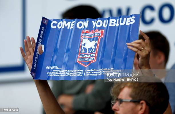 An Ipswich Town fan holds a banner in the stands before the game
