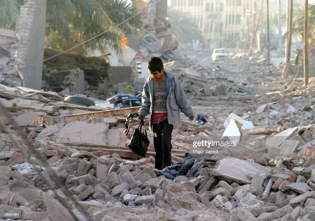An Iranian boy carrying a bag walks through the street of his destroyed neighborhood December 28, 2003 in Bam, Iran. An earthquake registering 6.5 on the Richter scale hit the southeast Iranian town of Bam December 26, killing around 20,000, with rescue officials stating that the figure could eventually double.