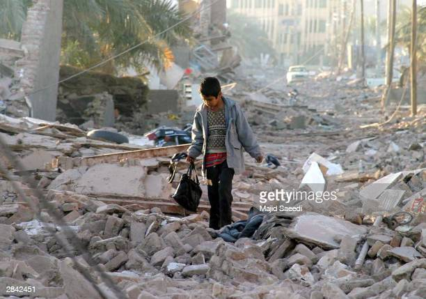 An Iranian boy carrying a bag walks through the street of his destroyed neighborhood December 28 2003 in Bam Iran An earthquake registering 65 on the...