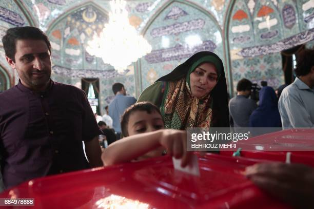TOPSHOT An Iranian boy casts his mother's ballot for the presidential elections at a polling station in Tehran on May 19 2017 / AFP PHOTO / Behrouz...
