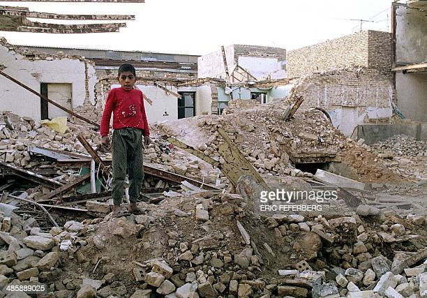 An Iranian boy stands 25 January 1987 on the ruins of his house in Ahvaz destroyed 23 January by an Iraqi air raid during the 'war of the cities' as...