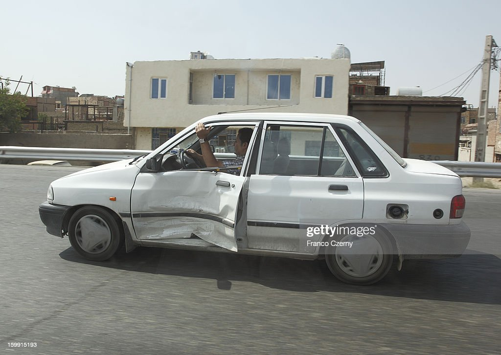 An iranian car driver holds the damaged door of his car as he drives on a highway on August 14, 2012 in Tehran, Iran.