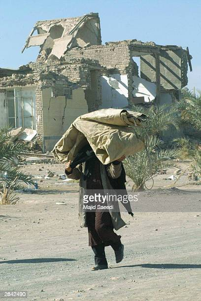 An Iranian carries tarps as he walks before buildings destroyed by last week's earthquake January 3 2004 in Bam Iran The death toll from the...