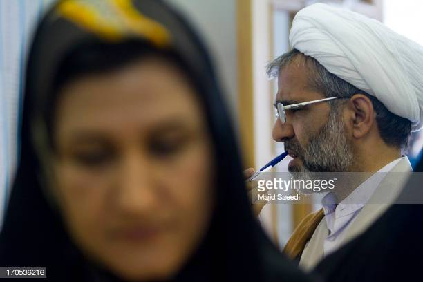An Iranian Clergy views the list of candidates before casting his vote at a polling station during the first round of the presidential election on...
