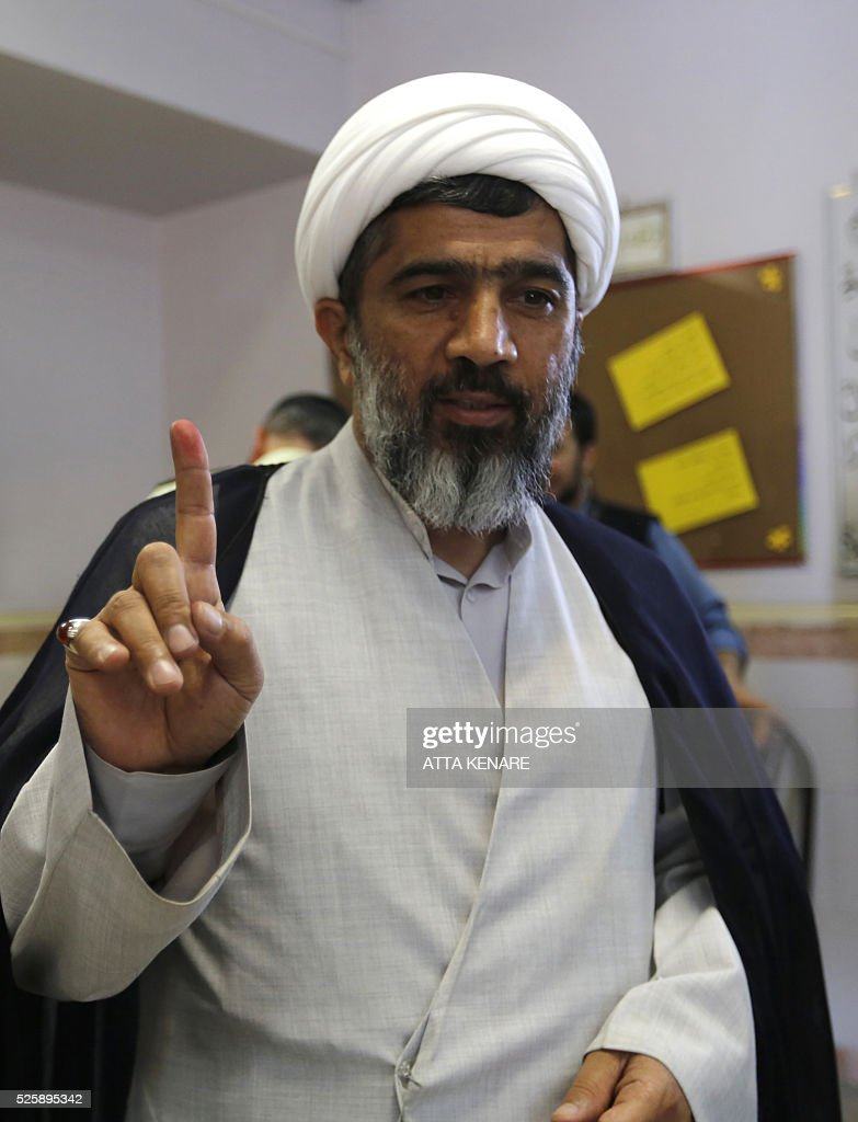 An Iranian cleric displays his ink-stained finger after casting his ballot for the second round of parliamentary elections at a polling station in the town of Robat Karim, some 40 kms southwest of the capital Tehran, on April 29, 2016. Iranians started voting in second round elections for almost a quarter of parliament's seats, the latest political showdown between reformists and conservatives seeking to influence the country's future. Polling stations opened at 8:00 am (0330 GMT) for the ballot which is taking place in 21 provinces, but not Tehran, because no candidate in 68 constituencies managed to win 25 percent of votes cast in initial voting on February 26. Reformists who backed moderate President Hassan Rouhani made big gains in the first round following Iran's implementation of a nuclear deal with world powers, which lifted sanctions blamed for long hobbling the economy. Conservative MPs, including vehement opponents of the West who openly criticised the landmark agreement that reined in Iran's atomic programme, lost dozens of seats and were wiped out in Tehran where reformists won all 30 places in parliament. / AFP / ATTA