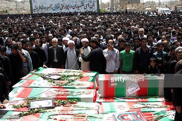 An Iranian cleric prays over the coffins of the victims of twin suicide bombings targeting a Shiite mosque during a mass funeral in the southeastern...