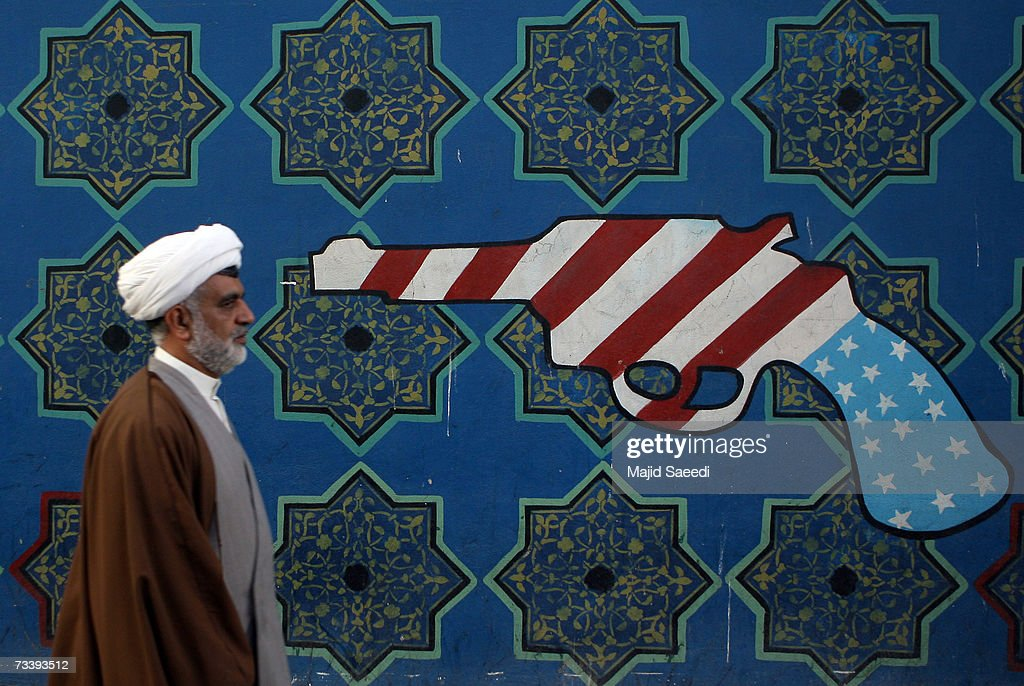 An Iranian clerric walks past a mural on the wall of the former US embassy apparently undaunted by media reports of potential airstrikes by the US if...