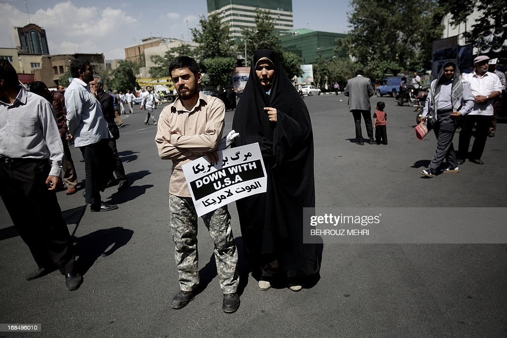An Iranian couple holding an anti-US sign listen to a speech during an anti-Israeli demonstration at Palestine Square in Tehran on May 10, 2013 to condemn last week's Israeli air strikes near the Syrian capital Damascus. Iran has condemned the Israeli strikes and said it is ready to train the Syrian army, which is in its third year of a conflict against rebels seeking to overthrow Bashar al-Assad.
