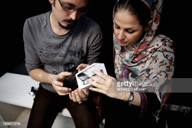 An Iranian couple inpect the box of an IPhone they just bought at a computer shop selling Apple products in northern Tehran on June 1 2013 The United...