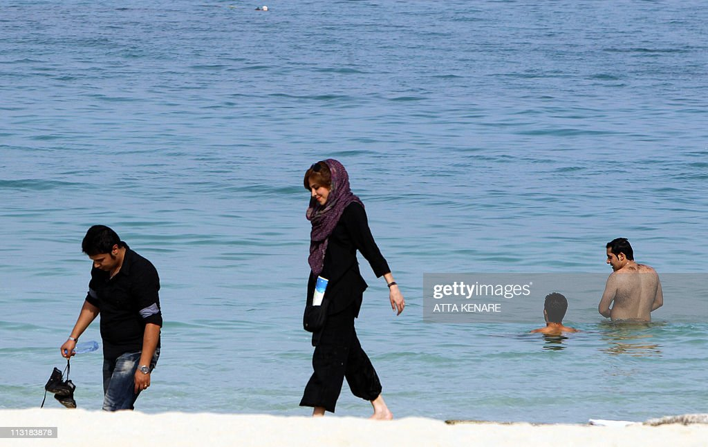 An Iranian couple walk on the beach in K Pictures Getty Images