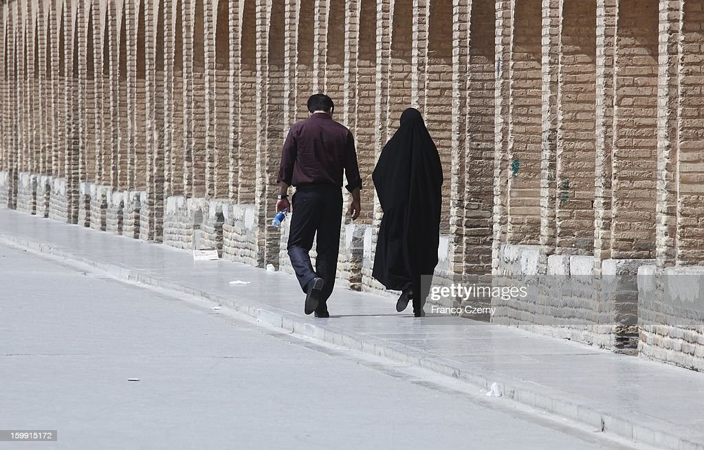 An iranian couple walk past the si-o-seh bridge, or the Bridge of 33 Arches on August 16, 2012 in Isfahan, Iran.