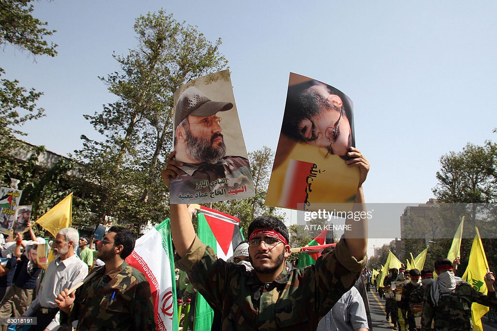 An Iranian demonstrators dressed in a military fatigue holds a portraits of Lebanon's Hezbollah chief Hassan Nassrallah and his slain comrade Imad...