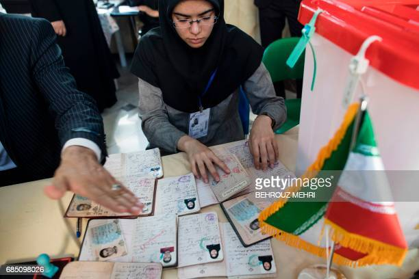 An Iranian election official checks ID cards of voters for the presidential elections at a polling station in Tehran on May 19 2017 / AFP PHOTO