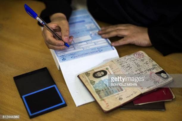 An Iranian election official registers a voter during the parliamentary and Assembly of Experts elections at a polling station in the holy city of...