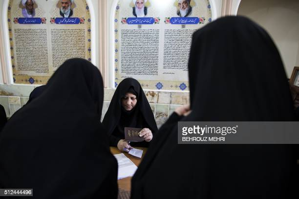 TOPSHOT An Iranian election official registers voters for parliamentary and Assembly of Experts elections at a polling station at Massoumeh shrine in...