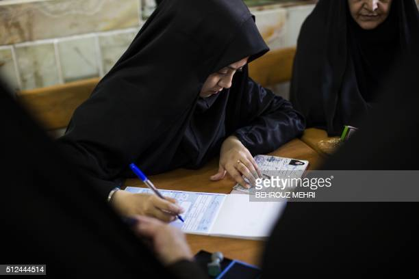 An Iranian election official registers voters for parliamentary and Assembly of Experts elections at a polling station at Massoumeh shrine in the...