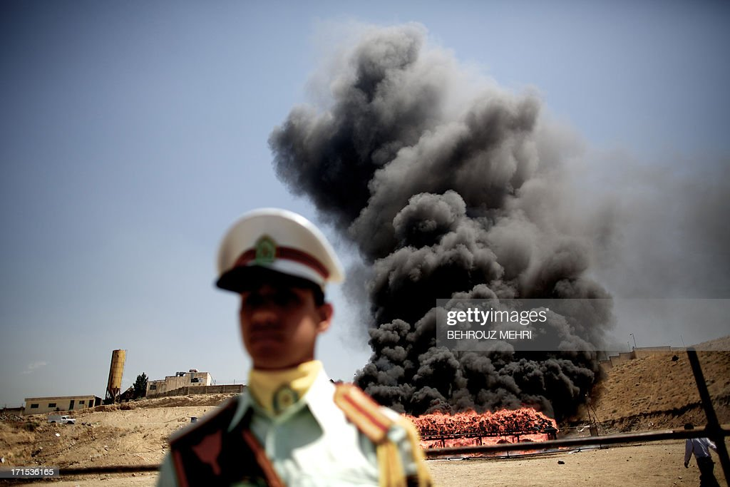 An Iranian employee of the anti-drug police watches 50 tons of drugs seized in recent months burning in eastern Tehran on June 26, 2013 to mark the International Day Against Drug Abuse and Illicit Trafficking.
