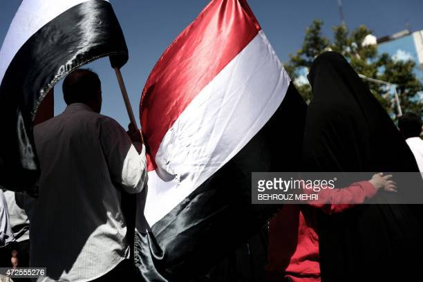 An Iranian family holds Yemeni national flags as they take part in a demonstration in Tehran on May 8 following the weekly Friday prayers to denounce...
