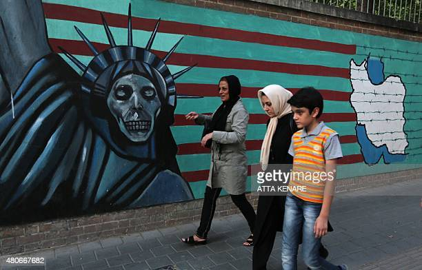 An Iranian family walks past antiUS graffiti on the wall of the former US embassy in Tehran on July 14 2015 President Hassan Rouhani told Iranians...
