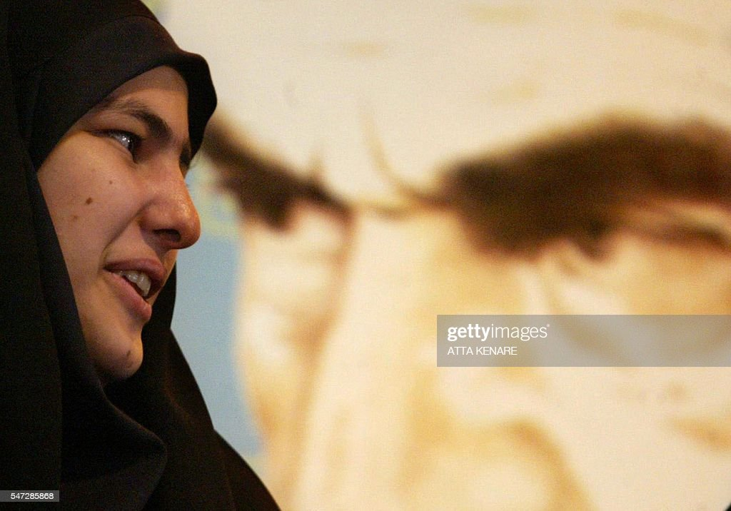 An Iranian female student a member of the hardline Basij Islamic militia speaks to a friend as she stand in front of a picture of the late Iranian...