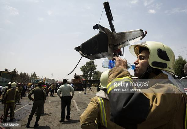 An Iranian fireman drinks water while relocating the remains of a plane at the site of a crash near Tehran's Mehrabad airport on August 10 2014 An...