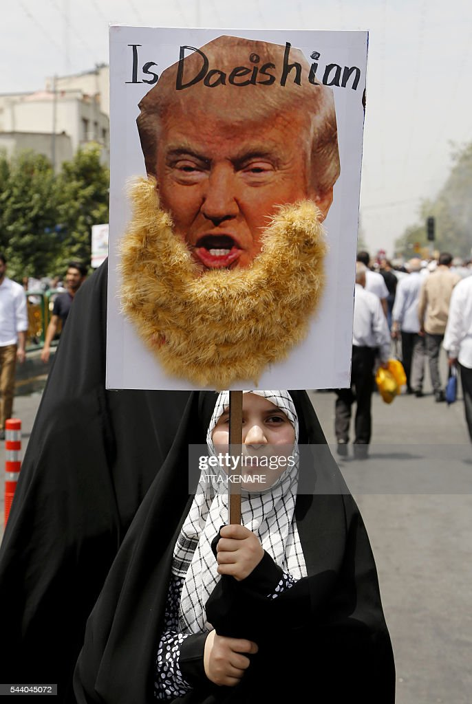 An Iranian girl holds up a portrait of US Republican presidential candidate Donald Trump adorned with jihadist-style beard and a slogan reading 'is Daeishian' (Daesh is Arabic acronym for Islamic State), during a parade marking al-Quds (Jerusalem) Day in Tehran on July 01, 2016. Tens of thousands joined pro-Palestinian rallies in Tehran, as the annual Quds Day protests take on broader meaning for a region mired in bitter disputes and war. KENARE