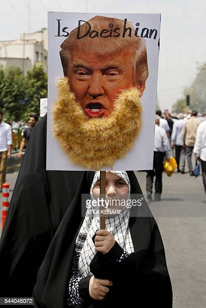 An Iranian girl holds up a portrait of US Republican presidential candidate Donald Trump adorned with jihadiststyle beard and a slogan reading 'is...