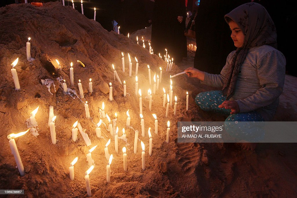 An Iranian girl lights a candle next to the Imam Hussein shrine as part of the ritual ceremony of Ashura in Karbala, 80 km (50 miles) southwest of Baghdad, on November 25, 2012. Millions of pilgrims pour into the Iraqi shrine city of Karbala for the peak of commemorations for Ashura today, the most important day in the Shiite calendar, with security tight following mass-casualty attacks in previous years.