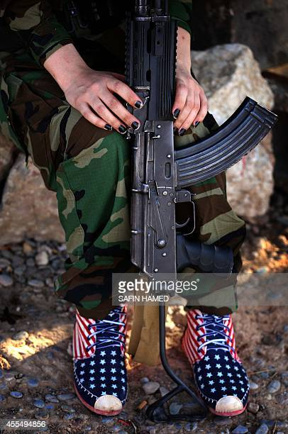 An Iranian Kurdish female member of the Freedom Party of Kurdistan sits with her weapon in Dibis some 50 kms northwest of Kirkuk on September 15 2014...
