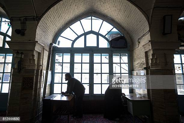 An Iranian man and a woman check the names of candidates from the list before voting for the parliamentary and Assembly of Experts elections at a...