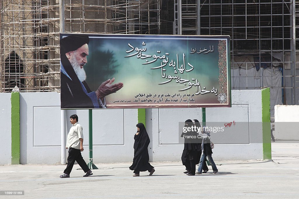 An Iranian man and iranian women in chador walk past the Holy Shrine mausoleum of Ayatollah Khomeini on August 14, 2012 in Tehran, Iran.