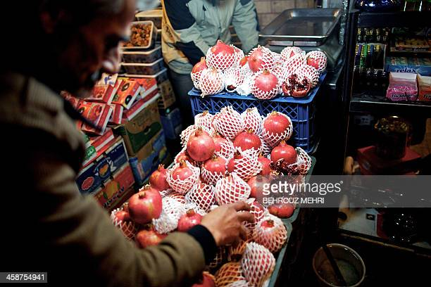 An Iranian man arranges pomegranates in his shop in downtown Tehran on December 21 in preparation for the annual festival of Yalda an ancient...
